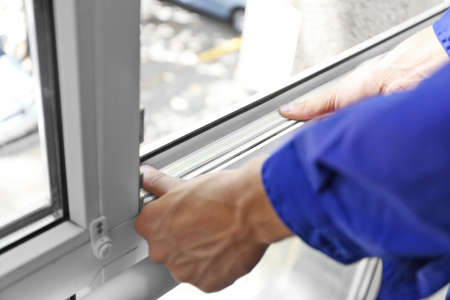 Photo for Construction worker putting sealing foam tape on window in house - Royalty Free Image