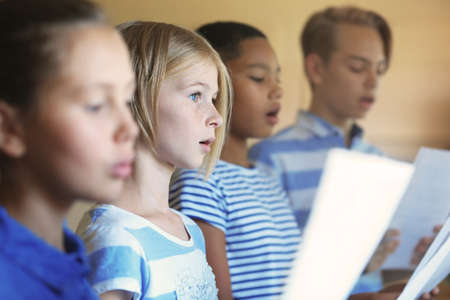 Foto de Schoolchildren singing song on music lesson - Imagen libre de derechos
