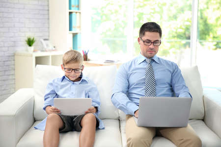 Photo for Little son with tablet and father with laptop sitting on sofa at home - Royalty Free Image