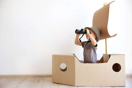 Photo pour Little boy playing with cardboard ship on white wall background - image libre de droit