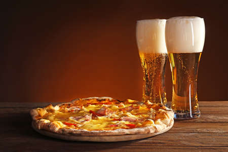 Photo pour Tasty pizza with beer on wooden table - image libre de droit