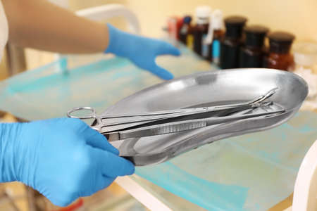 Foto de Doctor holding tools in steel basin, close up - Imagen libre de derechos