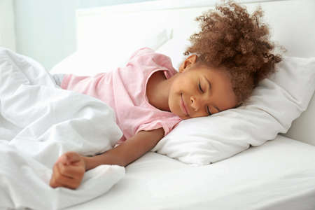 Photo for Little African American girl resting in bed - Royalty Free Image