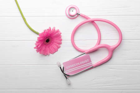 Foto de Business card with word GYNECOLOGIST, flower and stethoscope on white wooden background - Imagen libre de derechos
