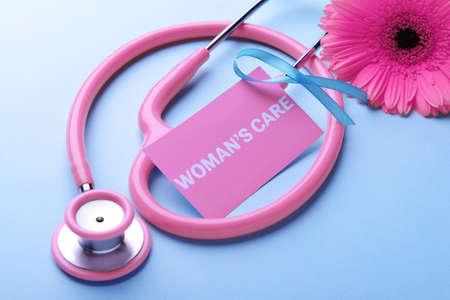 Foto de Business card with text WOMANS CARE, ribbon, flower and stethoscope on blue background - Imagen libre de derechos