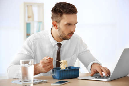 Photo for Young man eating instant noodles while working with laptop in office - Royalty Free Image