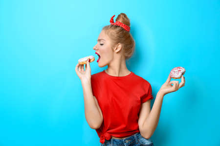 Foto de Young beautiful woman with doughnuts on blue background - Imagen libre de derechos