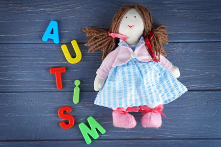 Foto de Word AUTISM with doll on wooden background - Imagen libre de derechos