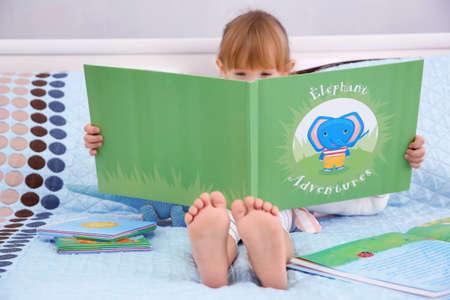 Foto de Little cute girl reading book - Imagen libre de derechos