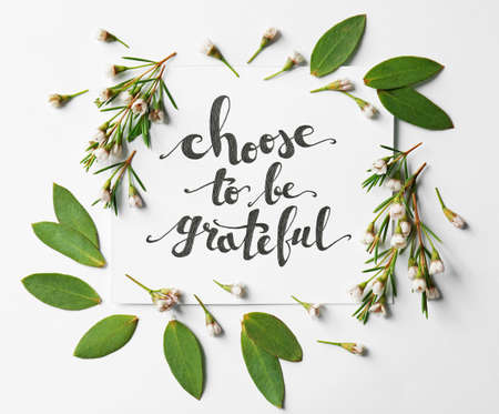 Foto de Quote Choose to be grateful written on paper with leaves and flowers on white background. Top view - Imagen libre de derechos