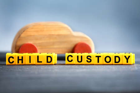 Photo pour Text CHILD CUSTODY made of yellow blocks with wooden car on table against blurred background, closeup - image libre de droit