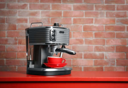 Photo pour New electric coffee maker on brick wall background - image libre de droit