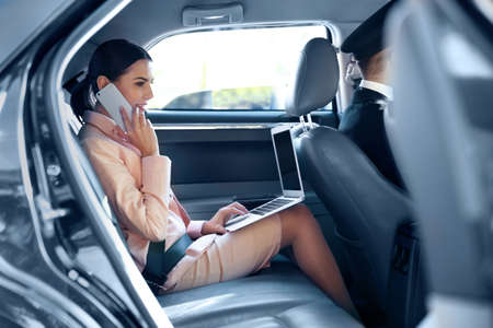 Photo pour Businesswoman speaking by cellphone and riding a car - image libre de droit