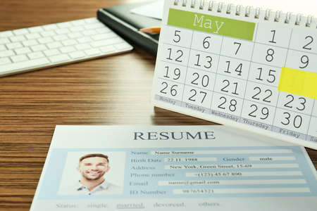 Foto de Calendar with job interview reminder and resume on wooden table - Imagen libre de derechos