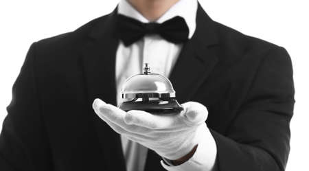 Photo pour Bellboy holding bell on his hand, close up - image libre de droit