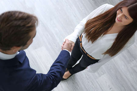 Photo for Employer and applicant shaking hands after interview, top view - Royalty Free Image