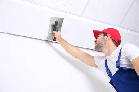 Photo pour Young worker making repair in room - image libre de droit