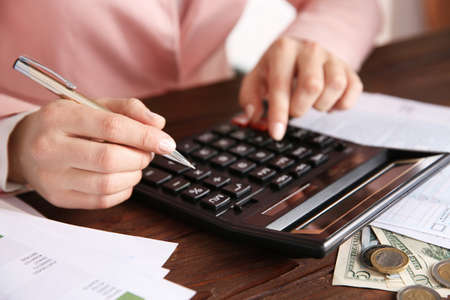 Foto de Woman sitting at table with calculator and documents - Imagen libre de derechos