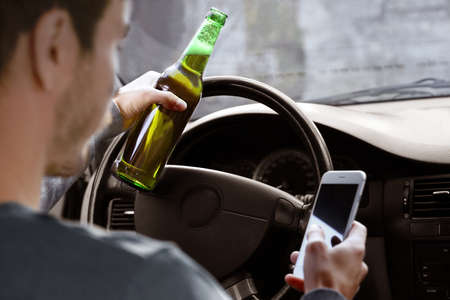 Photo for Man holding mobile phone and bottle of beer while driving car, closeup. Don't drink and drive concept - Royalty Free Image