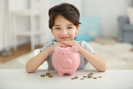 Photo pour Portrait of cute little boy with piggy bank on blurred background - image libre de droit