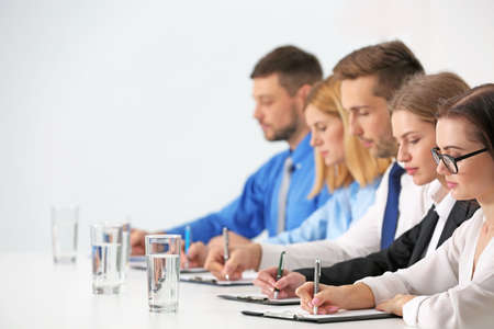 Photo pour Human resources team sitting in a row at table in office - image libre de droit