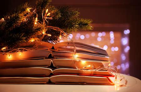 Foto de Pile of open books, coniferous branch and garland, closeup - Imagen libre de derechos