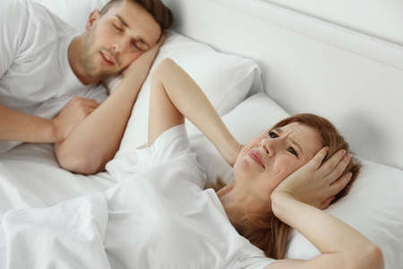 Photo pour Young girl can't sleep because of her man's snoring - image libre de droit