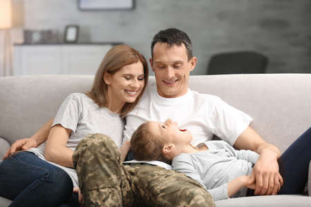 Photo pour Military father with his family on sofa at home - image libre de droit