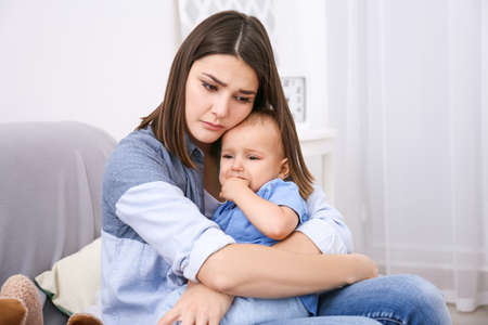 Photo for Depressed young woman with cute baby at home - Royalty Free Image