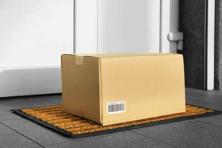 Photo for Parcel in cardboard box left on door step - Royalty Free Image