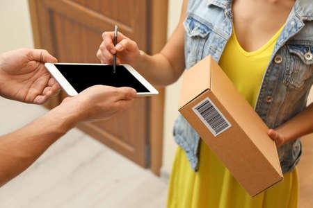 Foto für Young woman appending signature after receiving parcel from courier at home, closeup - Lizenzfreies Bild