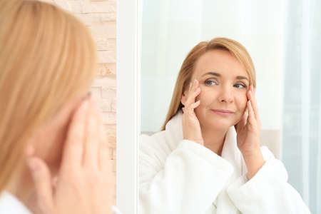 Foto de Happy senior woman applying anti-aging cream near mirror - Imagen libre de derechos