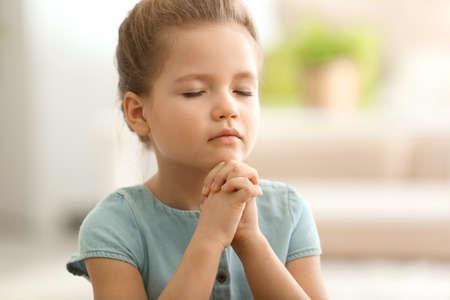 Foto de Cute little girl praying at home - Imagen libre de derechos