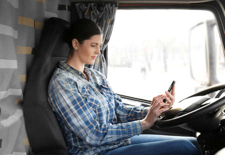 Foto per Young female driver sitting in cabin of big modern truck - Immagine Royalty Free