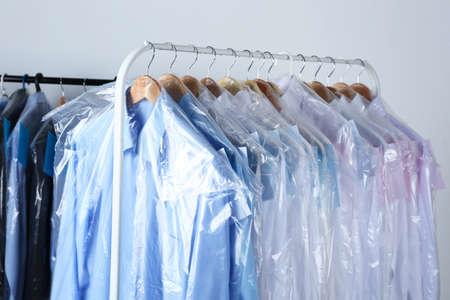 Foto für Rack of clean clothes hanging on hangers at dry-cleaning - Lizenzfreies Bild