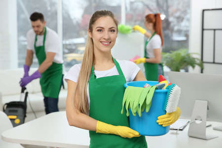 Photo for Young female worker holding cleaning supplies at office - Royalty Free Image