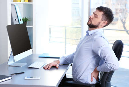 Foto de Posture concept. Man suffering from back pain while working with computer at office - Imagen libre de derechos