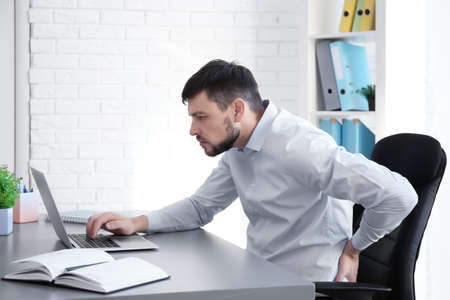 Foto de Posture concept. Man suffering from back pain while working with laptop at office - Imagen libre de derechos