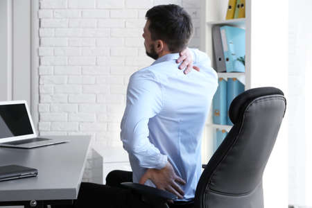 Photo for Posture concept. Man suffering from back pain while working with laptop at office - Royalty Free Image