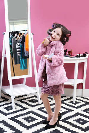 Photo pour Cute little girl playing with her mother's cosmetic at home - image libre de droit