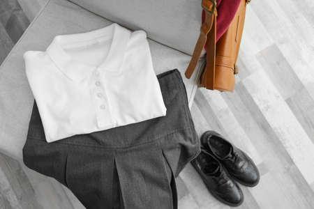 Photo pour Clothes of schoolgirl on chair , indoors - image libre de droit