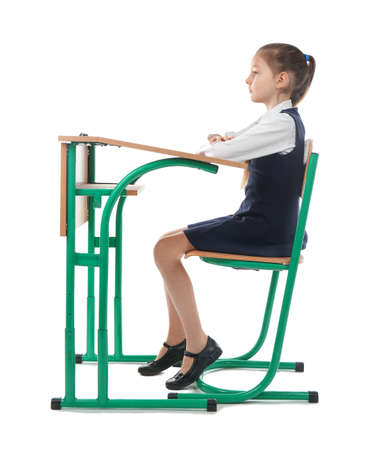 Photo for Incorrect posture concept. Little girl sitting at school desk on white background - Royalty Free Image