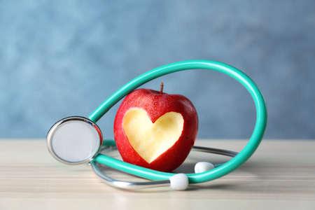Foto de Apple with stethoscope on color background - Imagen libre de derechos