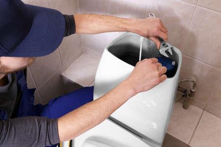 Foto de Plumber repairing toilet cistern at water closet - Imagen libre de derechos