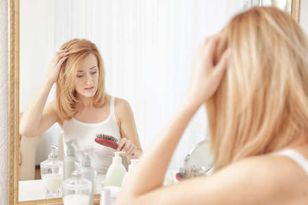 Photo for Young woman with hair loss problem in front of mirror at home - Royalty Free Image