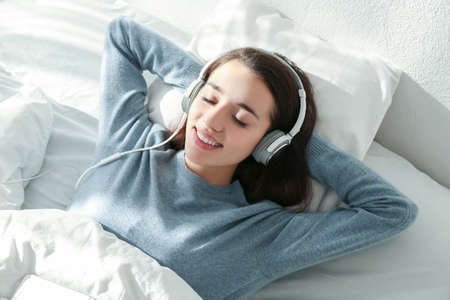 Photo pour Young woman listening to music in headphones on bed - image libre de droit