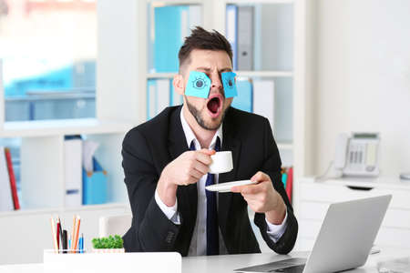 Foto de Young business man with fake eyes painted on paper stickers yawning at workplace in office - Imagen libre de derechos