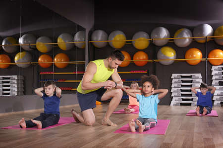 Photo for Children at physical education lesson in school gym - Royalty Free Image