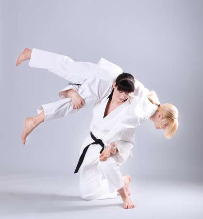 Photo pour Young sporty women practicing martial arts on light background - image libre de droit