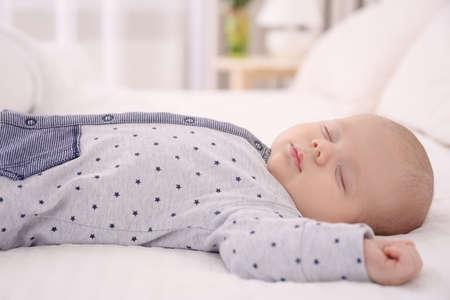 Foto de Cute little baby sleeping on bed at home - Imagen libre de derechos